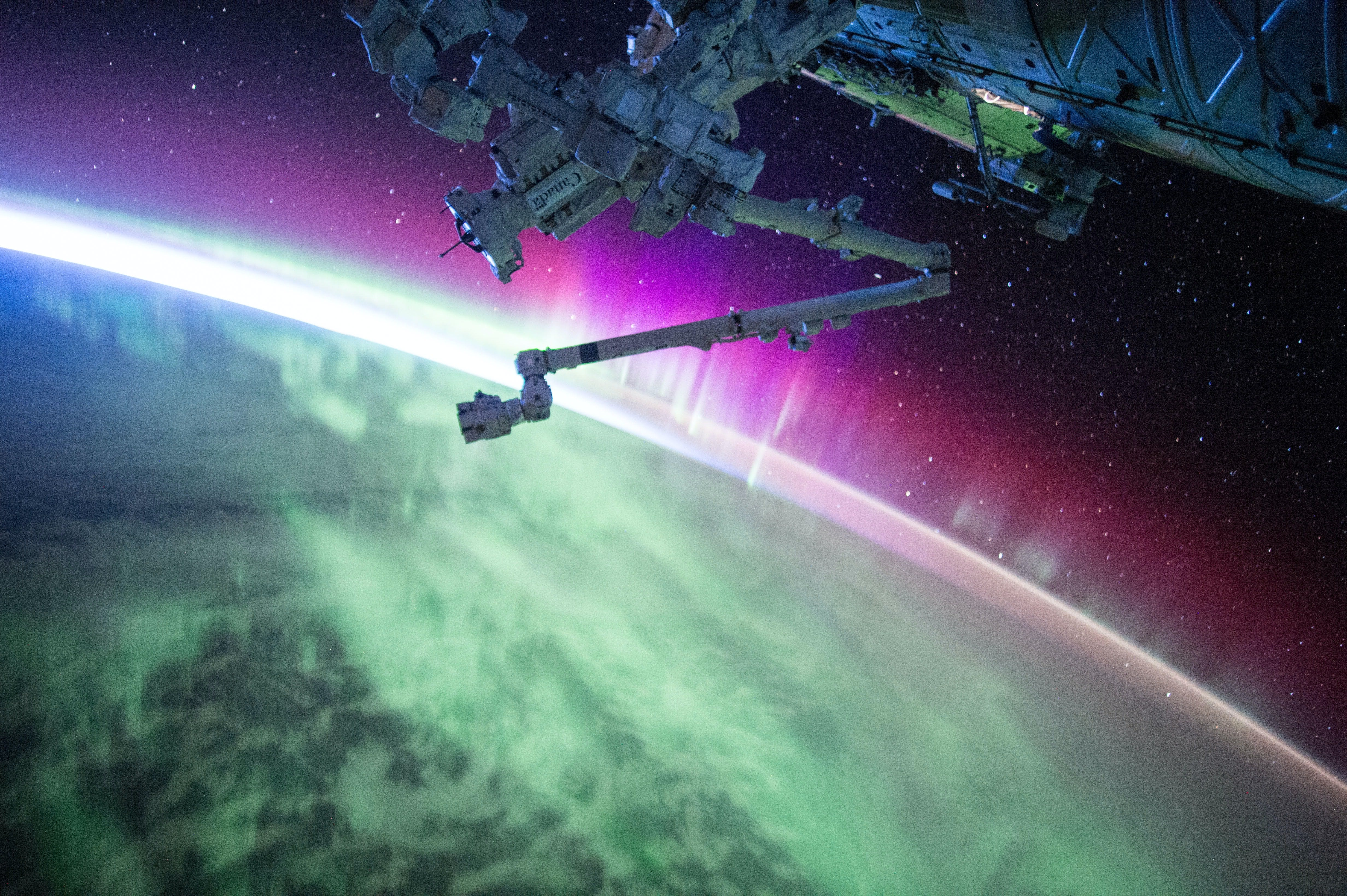 NASA spaceship arm extended above earth