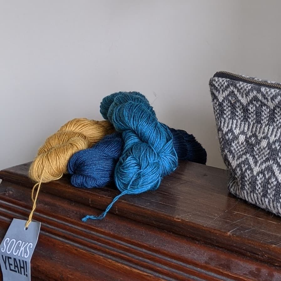 three skeins of yarn sat on a wooden box with a grey wool project bag