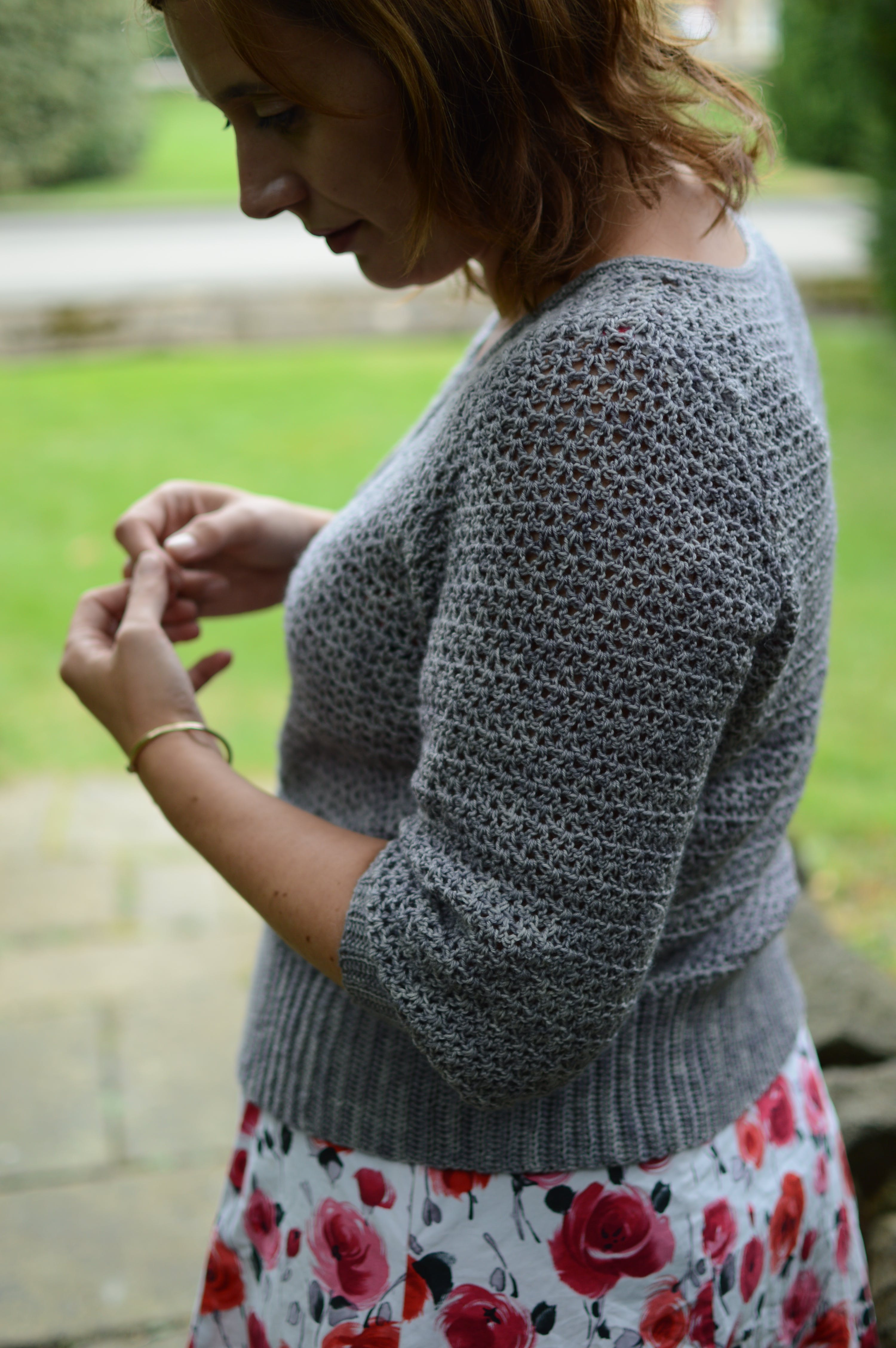joanne wears a grey Alyssium cardigan, she is turned to the side with shoulder visible, indestinct background