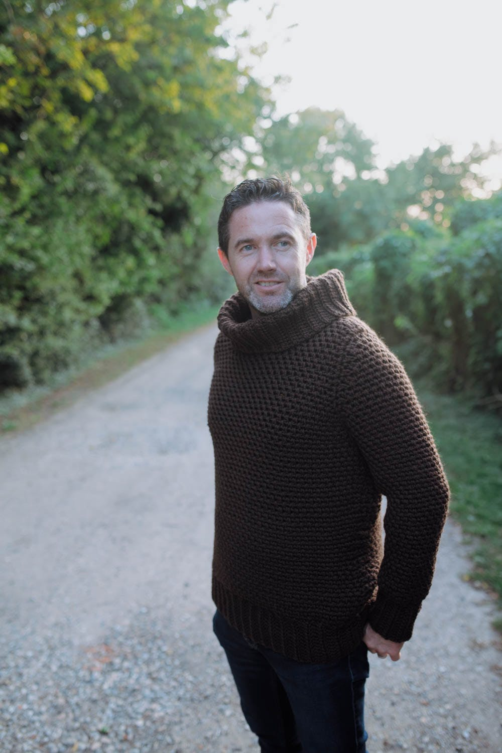 kenny wears brown jumper facing camera against a leafy background