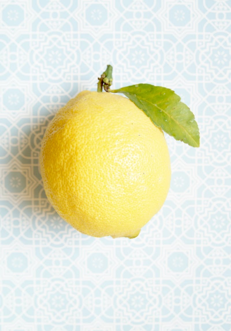 yellow lemon fruit on white and blue textile