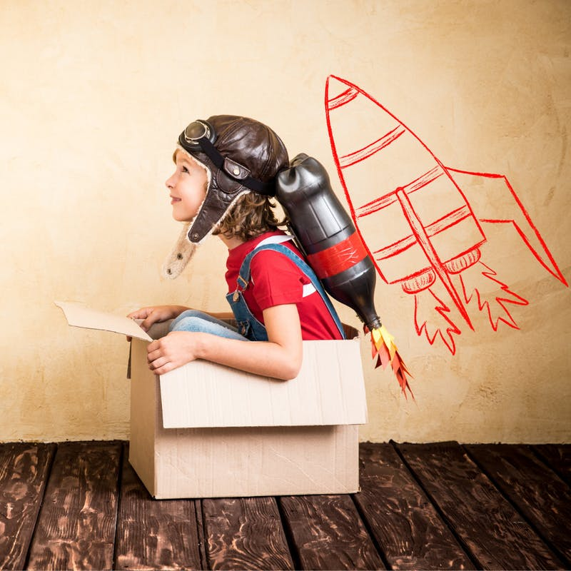 a child sitting in a cardboard box pretending to be in a spaceship