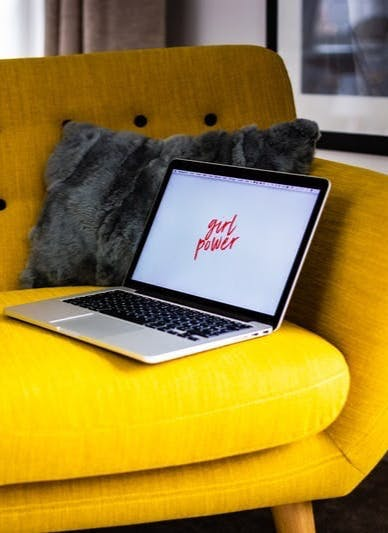 shallow focus photo of gray laptop computer on yellow couch