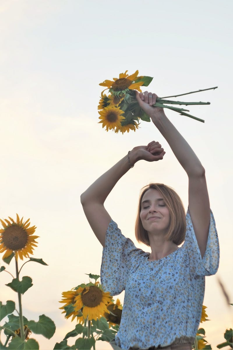 woman in blue and white floral dress holding sunflower