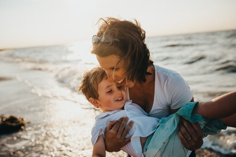 photo of mother and child beside body of water
