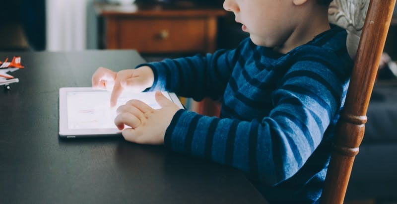 boy sitting on chair beside table using tablet computer