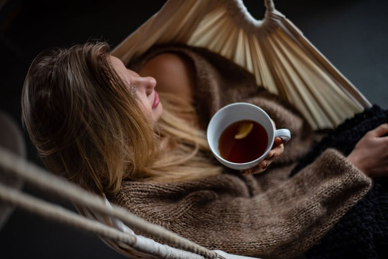 woman on hammock holding cup of coffee