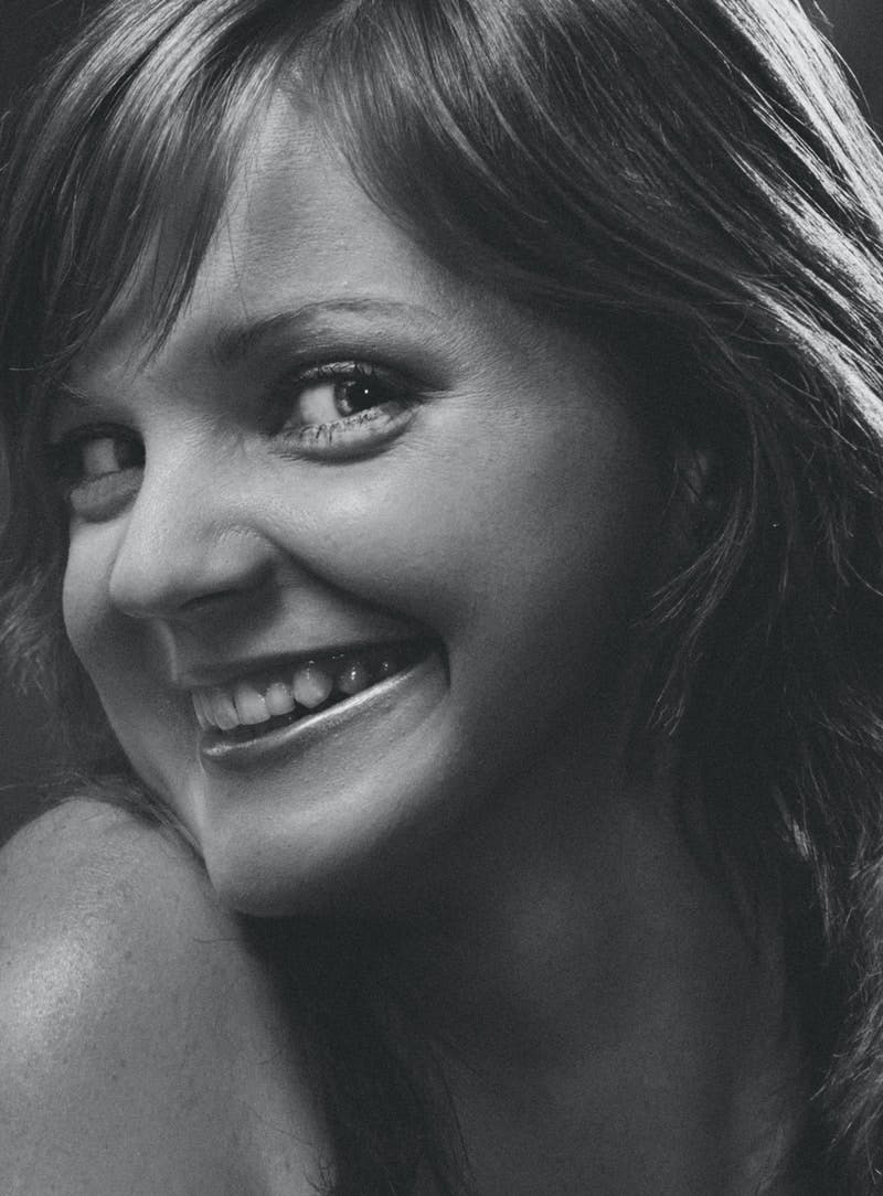 smiling woman in grayscale photo