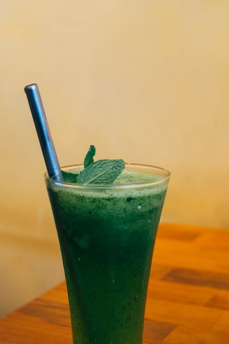 clear drinking glass with green liquid and straw