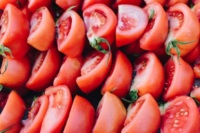 red sliced tomato in close up photography