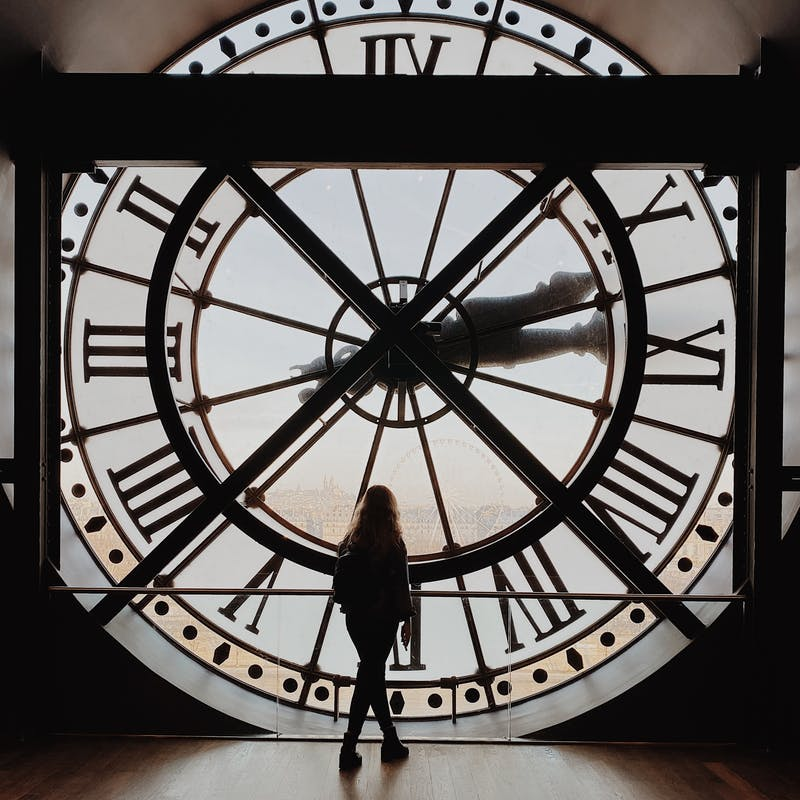 a woman standing in front of a clock intending that time slows down