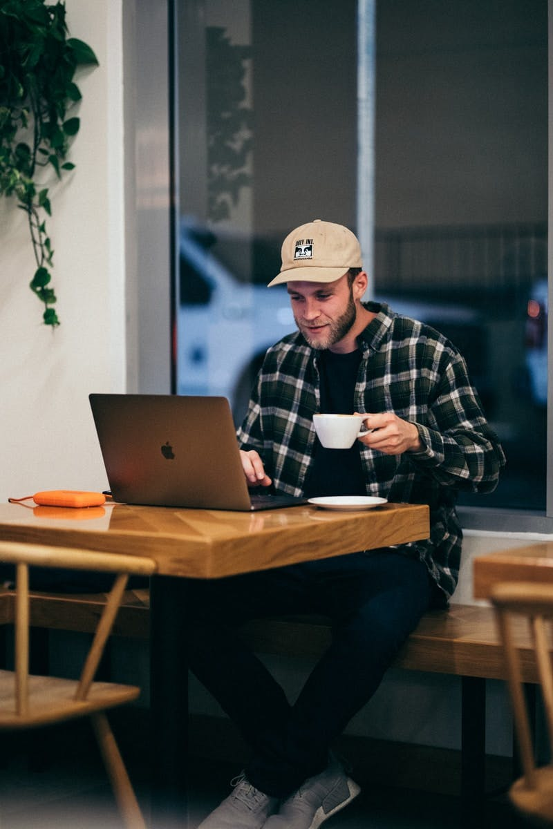 man sitting while having coffee and using laptop