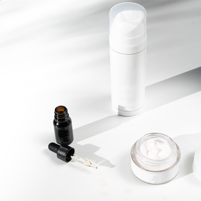 black and orange bottle beside white round container