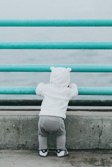 toddler standing while resting arm on rail facing body of water