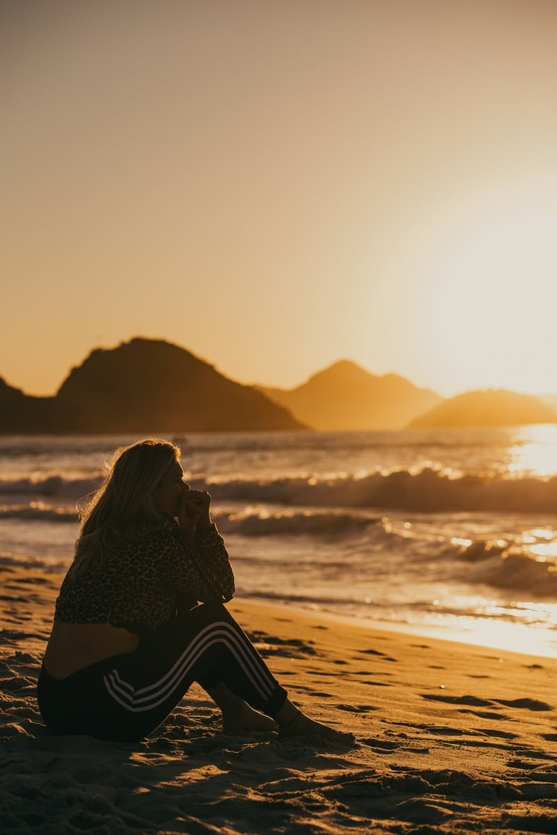 woman in black and white dress sitting on beach during sunset