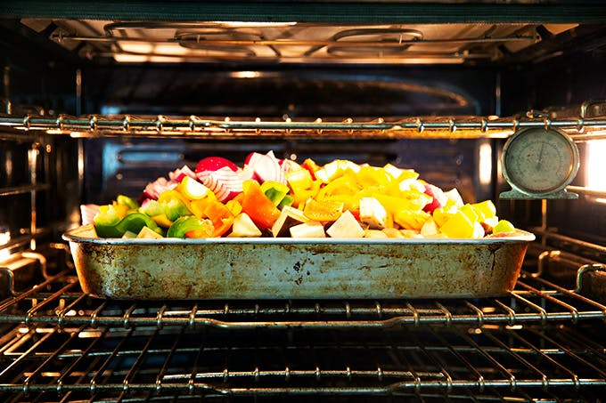 A pan of vegetables in the oven.