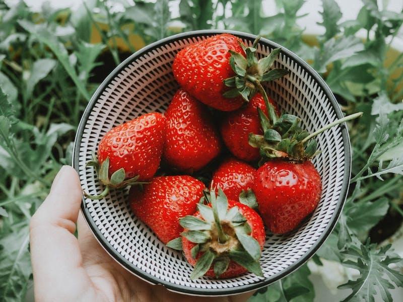 strawberries on white and black round basket